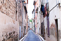 Village street with washing hanging to dry. Agde town. Languedoc. France. Europe.