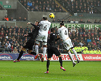 Wednesday, 01 January 2014<br /> Pictured L-R: Ashley Williams (6) and Chico Flores (4) of Swansea attempt to get a header in from a team mates cross. <br /> Re: Barclay's Premier League, Swansea City FC v Manchester City at the Liberty Stadium, south Wales.