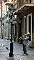 New Orleans street scene of a saxophonist playing in the French Quarter's Exchange Alley. French Quarter, New Orleans, Louisiana.