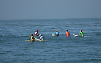 The surfers wait during a lull in the Final heat