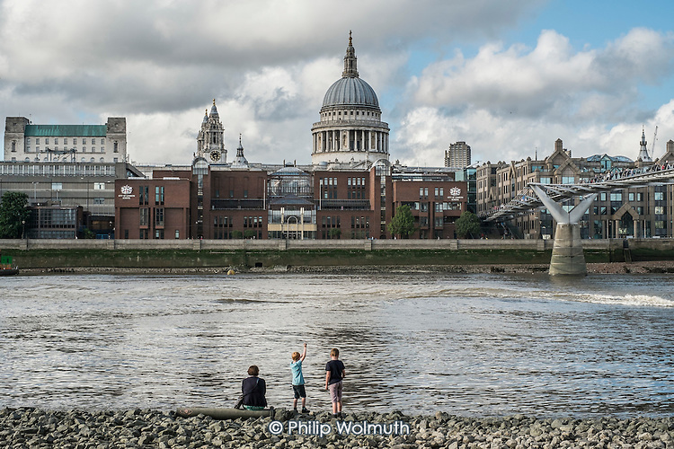 Children playing at low tide on the Thames opposite St Pauls Cathedral London.