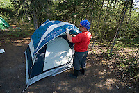 Nick Lynch sets up his tent at a camp along the Kenai River