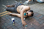 © Joel Goodman - 07973 332324 - all rights reserved . 25/08/2019. Manchester, UK. A man lies on the ground with a condom in his mouth as he reaches out for another condom on the pavement . Revellers in Manchester's Gay Village during the city's annual Gay Pride festival , which celebrates LGBTQ+ life and is the largest of its type in Europe . Photo credit : Joel Goodman