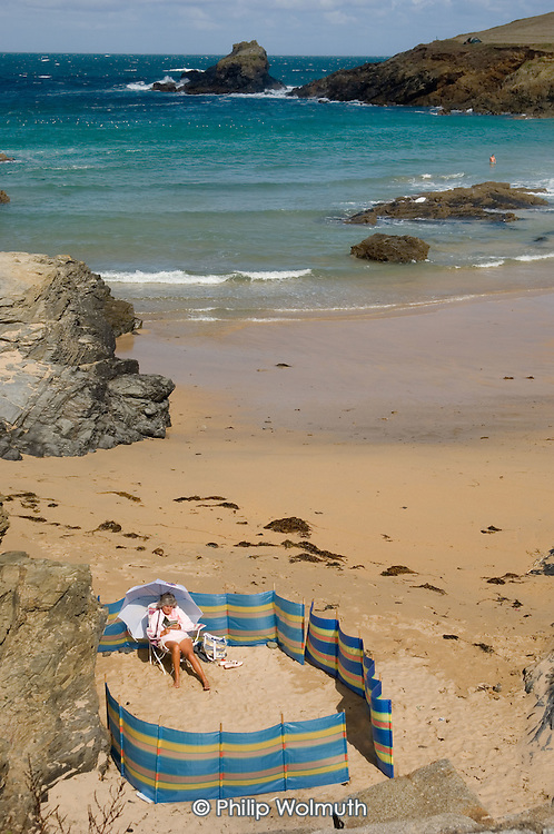 A woman shelters from high winds on the beach at Trevone, in North Cornwall.