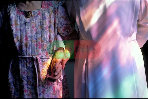 nun holding hand of elder woman walking in nursing home