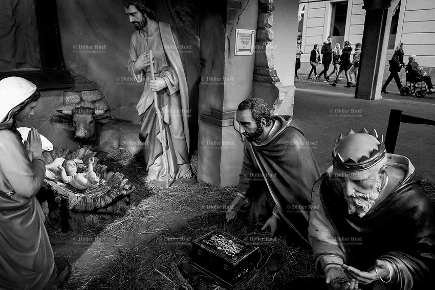 """Switzerland. Canton Ticino. Lugano. A nativity scene in the city center. In the Christian tradition, a nativity scene (also known as a manger scene, crib, crèche, or in Italian presepio or presepe) is the special exhibition, particularly during the Christmas season, of art objects representing the birth of Jesus. While the term """"nativity scene"""" may be used of any representation of the very common subject of the Nativity of Jesus in art, it has a more specialized sense referring to seasonal displays, using model figures in a setting. Nativity scenes exhibit figures representing the infant Jesus, his mother, Mary, and her husband, Joseph. Other characters from the nativity story, such as shepherds, sheep, and angels may be displayed near the manger in a barn (or cave) intended to accommodate farm animals, as described in the Gospel of Luke. An ox  and the Magi. The biblical Magi, also referred to as the (Three) Wise Men or (Three) Kings, were – in the Gospel of Matthew and Christian tradition – distinguished foreigners who visited Jesus after his birth, bearing gifts of gold, frankincense and myrrh. They are regular figures in traditional accounts of the nativity celebrations of Christmas and are an important part of Christian tradition. A woman on a wheelchair and people walking on the street. 1.01.2020  © 2020 Didier Ruef"""