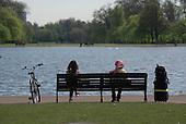Two women sitting on a park bench, Kensington Gardens, London.
