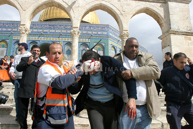 A Palestinian medic and a civilian assist a Palestinian man bleeding from his head as they remove him from near the Dome of the Rock, behind, during running clashes between Palestinians and Israeli policemen on the compound known to Muslims as the Noble Sanctuary and to Jews as the Temple Mount in Jerusalem's Old City February 24, 2012. Israeli policemen stormed the compound on Friday following prayers, using stun grenades to disperse stone-throwing Palestinian protesters, some of whom then retreated into al-Aqsa mosque. Israeli police spokesperson said 11 policemen were lightly injured from stones and 4 protesters were arrested. Photo by Mahfouz Abu Turk