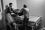 Gaza, Beach Camp: After an outing, Nour's father and cousin put him back in his bed; a movement that causes him pain in the shoulder, November 3, 2019<br /> <br /> Gaza, Beach Camp: Après une sortie, le père et le cousin de Nour le remette dans son lit; un mouvement qui lui cause de la douleur dans l'épaule, le 3 novembre 2019.