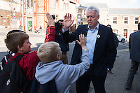MAESTEG, Wales. 4th May 2016. On the eve of the Welsh Assembly election, Labour leader Jeremy Corbyn and First Minister of Wales Carwyn Jones visit Maesteg, which will also hold a Westminster by-election for the Ogmore constituency tomorrow.<br /> <br /> Pictured: Carwyn Jones give high fives to three young boys before Corbyn's arrival