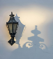 A fine art detail of a black early American cast iron street lantern casting shadows on a white stucco wall.