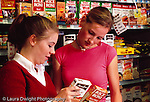 College students females shopping at supermarket, reading label on rice box