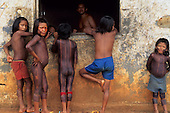 A-Ukre, Brazil. Kayapo Indian children with black genipapo body paint at the window of the Funai post. Para State.