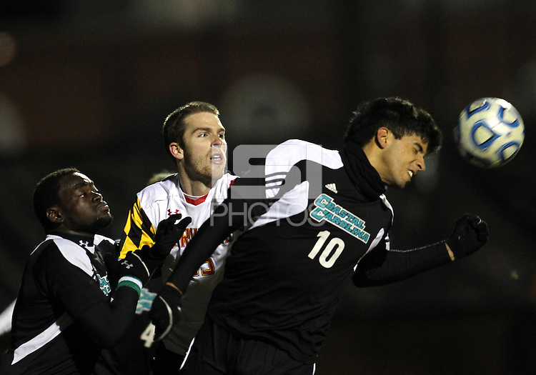 COLLEGE PARK, MD - NOVEMBER 25, 2012: Patrick Mullins (15) of the University of Maryland watches Pedro Ribeiro (10) of Coastal Carolina University head clear during an NCAA championship third round match at Ludwig Field, in College Park, MD, on November 25. Maryland won 5-1.