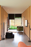 Floor to ceiling windows at one end of the wood-clad living area have a view of the garden