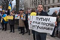 """Solidaritaets-Kundgebung fuer die Ukraine vor der Russischen Botschaft in Berlin.<br />Etwa 100 Menschen versammelten sich am Montag den 17. Maerz 2014 vor der Russischen Botschaft in Berlin um gegen die Politik der Russischen Praesidenten Putin und die Entscheidung des Referendums auf der Krim fuer eine Angliederung an Russland zu demonstrieren.<br />Unter den Kundgebungsteilnehmern waren auch die Europaabgeordnete  von B90/Die Gruenen Rebecca Harms und die Bundestagsabgeordnete von B90/Die Gruenen Marie-Luise Beck.<br />Im Bild: Ein Demonstrant mit einem Schild: """"Haende weg von der Kraine"""" (sinngem.). <br />17.3.2014, Berlin<br />Copyright: Christian-Ditsch.de<br />[Inhaltsveraendernde Manipulation des Fotos nur nach ausdruecklicher Genehmigung des Fotografen. Vereinbarungen ueber Abtretung von Persoenlichkeitsrechten/Model Release der abgebildeten Person/Personen liegen nicht vor. NO MODEL RELEASE! Don't publish without copyright Christian-Ditsch.de, Veroeffentlichung nur mit Fotografennennung, sowie gegen Honorar, MwSt. und Beleg. Konto:, I N G - D i B a, IBAN DE58500105175400192269, BIC INGDDEFFXXX, Kontakt: post@christian-ditsch.de]"""