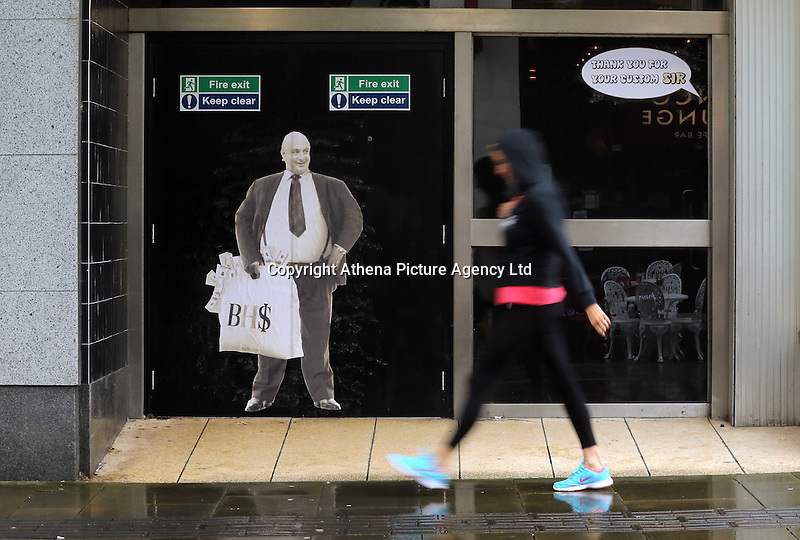 """Pictured: A woman walks by a poster of Sir Philip Green on the door of the now closed down BHS store in Oxford Street, Swansea, Wales, UK. Tuesday 13 September 2016<br /> Re: Former owner of BHS, Sir Philip Green has paid a surprise 'visit' to the closed down BHS store in Swansea.<br /> He was spotted in the doorway of the Oxford Street store, which closed its doors for the last time last month.<br /> In his hand was a BHS shopping bag with money spilling out of it.<br /> Sir Philip had owned BHS before selling it for £1 last year.<br /> He is claimed to have taken millions out of the company in dividends and left behind a £571m pensions deficit.<br /> Alongside the poster are the words: """"Thankyou for your custom Sir""""."""