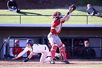 GREENSBORO, NC - FEBRUARY 25: Zak Budzik #2 of UNC Greensboro scores a run, beating the tag by Mike Caruso #19 of Fairfield University during a game between Fairfield and UNC Greensboro at UNCG Baseball Stadium on February 25, 2020 in Greensboro, North Carolina.