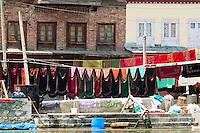 Colorful laundry hanging on lines along the shoreline of Dal Lake, Srinagar, Kashmir, India.