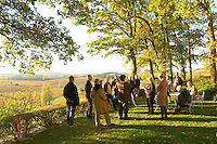A group of visitors in the garden at Chateau Belingard in autumn evening sunshine Chateau Belingard Bergerac Dordogne France