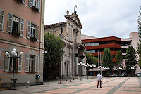 Chiasso, piazza Bernasconi. La chiesa di San Vitale tra il palazzo del comune e il moderno edificio della banca UBS --- Chiasso, Bernasconi square. The church of San Vitale between the building headquarter of the municipality and the modern edifice of the bank UBS