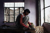 A man cuts pieces of leather in a small, informal leather factory in the city of Kanpur, India.
