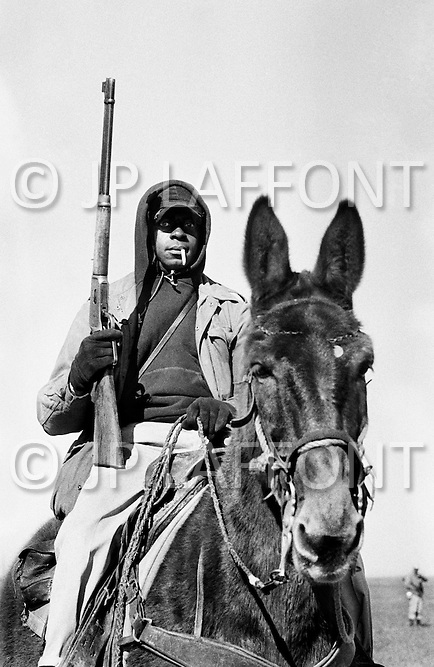 Cummings, AR. February 1968.<br /> A guard on horseback holds a rifle while watching inmates at the Cummins Unit of the Arkansas State Penitentiary.