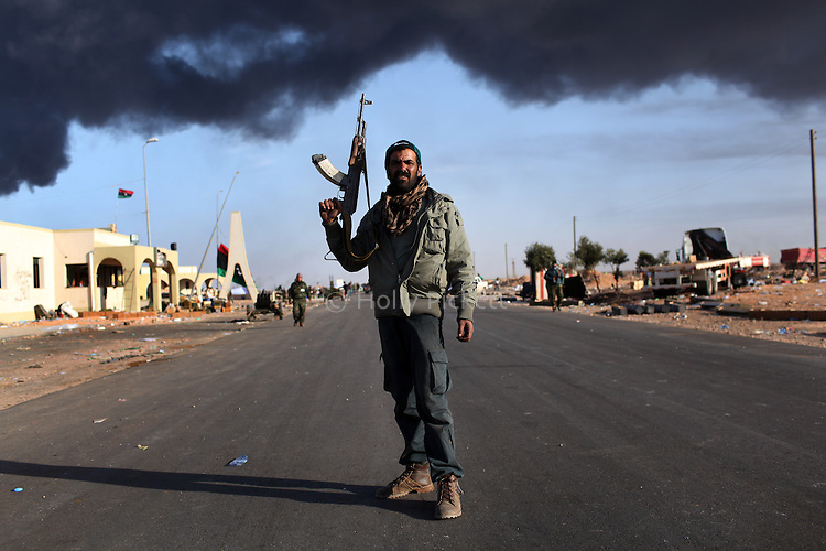 An opposition fighter pauses while pulling back near an oil refinery in Ras Lanuf, Libya, March, 11, 2011. Loyalist forces of Col. Muammar Qaddafi pushed rebels back from the strategic oil town with air strikes, artillery and small arms fire.