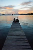 Honduras, Roatan Island, Fantasy Island Resort, Caribbean. Couple talking on the dock at sunset.