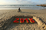 A Palestinian boy rides his bicycle past a 2018 sand writing at a beach in Gaza City on December 31, 2017 on the last day of the year. Photo by Ashraf Amra