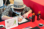 A man draws a traditional Japanese picture during the Moshi Moshi Nippon Festival 2016 on November 26, 2016 in Tokyo, Japan. Moshi Moshi Nippon Festival 2016 aims to promote Japanese pop culture (fashion, anime, technology, music and food) to the world, and non-Japanese visitors are able to enter the event for free by showing their passport. This year's two day event included live shows by Japanese pop stars Silent Siren, Dempagumi.inc, Tempura Kids, Capsule and Kyary Pamyu Pamyu at the Tokyo Metropolitan Gymnasium. (Photo by Rodrigo Reyes Marin/AFLO)