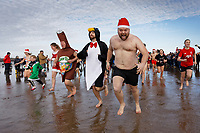 Pictured: People in fancy dress take to the sea. Wednesday 25 December 2019<br /> Re: Hundreds of people in fancy dress, have taken part in this year's Porthcawl Christmas Swim in south Wales, UK.