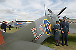 Goodwood Festival of Speed. Goodwood Sussex. UK. Couple reliving the past in retro clothes air display. Being photographed against a Spitfire MKX1V