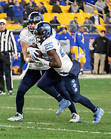 North Carolina running back Javonte Williams (25) gets a handoff from quarterback Sam Howell. The Pitt Panthers defeated the North Carolina Tarheels 34-27 in overtime in the football game on November 14, 2019 at Heinz Field, Pittsburgh, Pennsylvania.