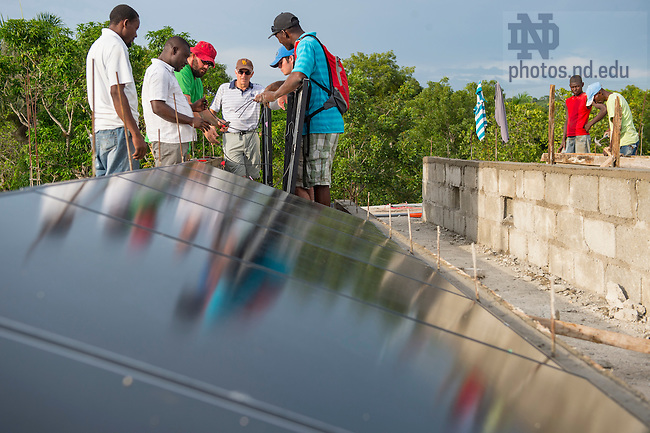 Aug. 11, 2015; Bill Jordan and Ken Oldrid, (center) from Let's Share The Sun Foundation, work with the solar panel installation crew on the roof at St. Gabriel School in Fontaine, Haiti. (Photo by Barbara Johnston/University of Notre Dame)