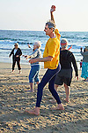 One tall senior male exercises with group of mature women in dance and exercise class on sandy Playa Del Rey beach in.Los Angeles, California
