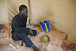 A young man in the fishing village of Yoff, Senegal keeps a watermelon buried in the sand under his beachside tent to keep it cool.