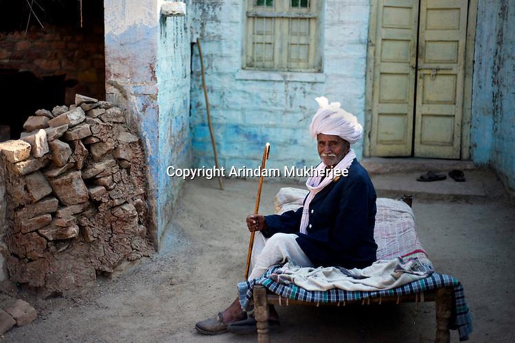 Jodha Ram Bishnoi sitting in front of his house at guda bishnoi village wearing taditional bishnoi dress. Jodhpur, Rajasthan, India. Arindam Mukherjee