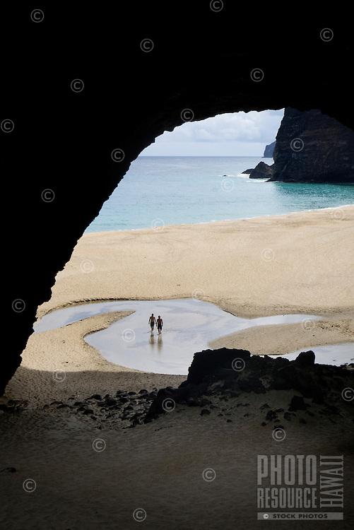 Two explorers wade through water at Honapu Beach on the Na Pali Coast, North Shore, Kaua'i.