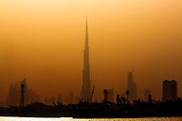 Foggy, colorful sunset over the Burj Khalifa and downtown skyline silhouettes, with the harbor in the foreground, Emirate of Dubai, Asia