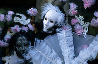 Portrait of two people wearing Venetian masks and costumes, Venice, Italy.