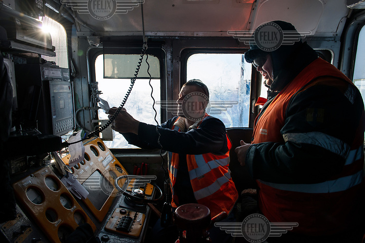 In the driver's cab of a locomotive on the Obskaya-Bovanenkovo railway, engineer Alexander Mironovich (L) checks a note from the duty officer that informs him the train is ready to depart to the Gasprom Bovanenkovo gas field.