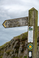 Northumberland,  England, UK.  Trail Marker for Pennine Way, where it departs from Hadrian's Wall Footpath.  Erosion Control Notice on Sign.