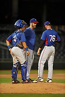 AZL Rangers pitching coach Bryan Conger visits with catcher Heriberto Hernandez (4) and relief pitcher Corey Stone (76) during an Arizona League game against the AZL Athletics Gold on July 15, 2019 at Hohokam Stadium in Mesa, Arizona. The AZL Athletics Gold defeated the AZL Rangers 9-8 in 11 innings. (Zachary Lucy/Four Seam Images)
