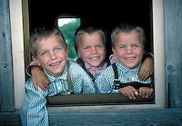 Three smiling young boys posing in window. Paul, Tom and Julius. Germany.