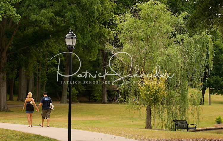 A couple holds hands as they walk down the path at Freedom Park in the Myers Park neighborhood in Charlotte, NC. Myers Park is one of the premier neighborhoods in North America and known for its large canopy of trees.
