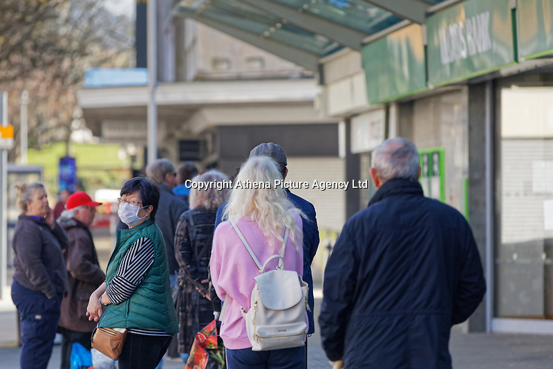 Pictured: A woman wearing a face mask stands in the queue outside Lloyds Bank in the city centre of Swansea, Wales, UK. Wednesday 25 March 2020 <br /> Re: Covid-19 Coronavirus pandemic, UK.