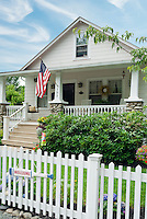 Lovely residential home with classic white picket fence and American flag on sunny summer day, with landscaping shrubs, lawn grass, curb appeal