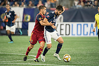 FOXBOROUGH, MA - SEPTEMBER 21: Justin Portillo #43 of Real Salt Lake comes in to tackle Carles Gil #22 of New England Revolution during a game between Real Salt Lake and New England Revolution at Gillette Stadium on September 21, 2019 in Foxborough, Massachusetts.