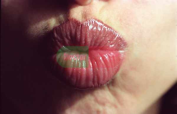 Close up of woman's (early 20s) lips puckered for a kiss